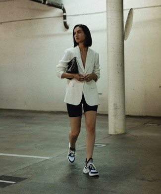 White Blazer Outfits For Women: This combo of a white blazer and black bike shorts combines comfort and definitely sass. Our favorite of a multitude of ways to finish this outfit is a pair of black and white athletic shoes.