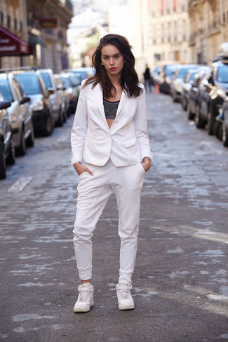 A silver cropped top and white track pants is a great combo to add to your casual lineup. A pair of white high top sneakers brings the dressed-down touch to the ensemble.