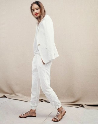 White Linen Tapered Pants Outfits For Women: A white blazer and white linen tapered pants worn together are a total eye candy for fashionistas who prefer relaxed combinations. Want to tone it down in the footwear department? Complement your outfit with a pair of clear embellished rubber flat sandals for the day.