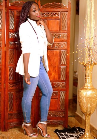If you're a fan of classic pairings, then you'll like this pairing of a white blazer and light blue skinny jeans. A cool pair of silver leather heeled sandals is an easy way to upgrade your look. Mastering transitional fashion is easy with style inspiration like this.