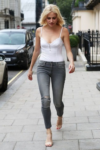 How to Wear Clear Rubber Heeled Sandals: A white bustier top and grey ripped skinny jeans are a nice combination to have in your off-duty styling lineup. On the fence about how to finish off? Introduce clear rubber heeled sandals to the equation to bump up the wow factor.