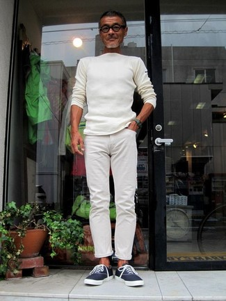 How to wear: white crew-neck sweater, white chinos, navy canvas low top sneakers, dark green watch