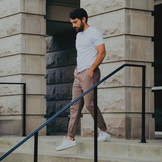 White and Red Leather Low Top Sneakers Casual Hot Weather Outfits For Men: For something more on the cool and casual end, team a white crew-neck t-shirt with brown vertical striped chinos. A great pair of white and red leather low top sneakers ties this look together.