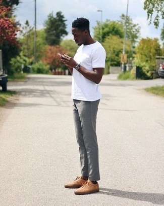 Tan Leather Low Top Sneakers Outfits For Men: For a look that offers practicality and style, pair a white crew-neck t-shirt with grey chinos. If you're puzzled as to how to finish off, a pair of tan leather low top sneakers is a winning option.