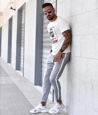How to wear: white print crew-neck t-shirt, grey chinos, white athletic shoes, navy sunglasses