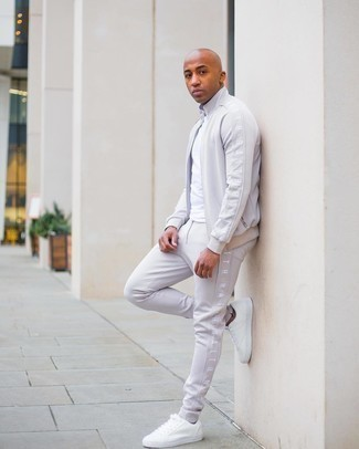 Track Suit Outfits For Men: Team a track suit with a white crew-neck t-shirt to achieve an incredibly sharp and casual ensemble. To bring some extra fanciness to your outfit, introduce white canvas low top sneakers to this ensemble.