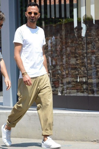 How to Wear Khaki Chinos: Marrying a white crew-neck t-shirt with khaki chinos is a savvy option for a casually cool getup. If you're on the fence about how to finish, a pair of white leather low top sneakers is a safe option.