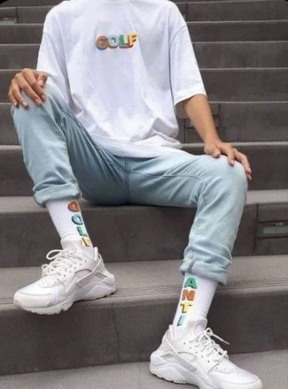 White Print Crew-neck T-shirt Outfits For Men: Inject style into your daily wardrobe with a white print crew-neck t-shirt and light blue jeans. Add a pair of white athletic shoes to your look to infuse an element of stylish effortlessness into this look.