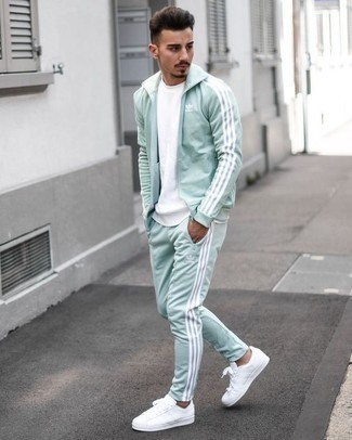 How to Wear a Track Suit For Men: Make a track suit and a white crew-neck t-shirt your outfit choice for a laid-back menswear style with a fashionable spin. Want to go all out on the shoe front? Complement this outfit with a pair of white canvas low top sneakers.