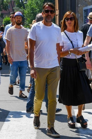 How to Wear Olive Chinos: Exhibit your prowess in menswear styling by putting together a white crew-neck t-shirt and olive chinos for a laid-back look. The whole getup comes together if you add a pair of black leather low top sneakers to this ensemble.