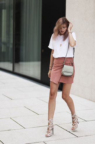 Pink Suede Mini Skirt Outfits: If you're on the hunt for a relaxed casual and at the same time seriously stylish look, try pairing a white crew-neck t-shirt with a pink suede mini skirt. A pair of beige leather heeled sandals will put a glamorous spin on an otherwise straightforward look.
