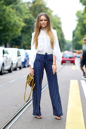 Look amazing without trying too much in a white oxford shirt and navy and white vertical striped drawstring pants. Dress up this look with heeled sandals. This combination is great when it's boiling hot outside.