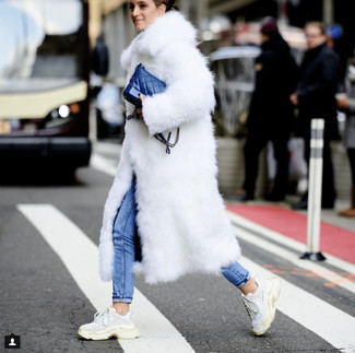 How to wear: white fur coat, blue skinny jeans, white athletic shoes, blue leather crossbody bag