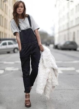 How to wear: white fur jacket, grey crew-neck t-shirt, black denim overalls, dark brown leather wedge sandals