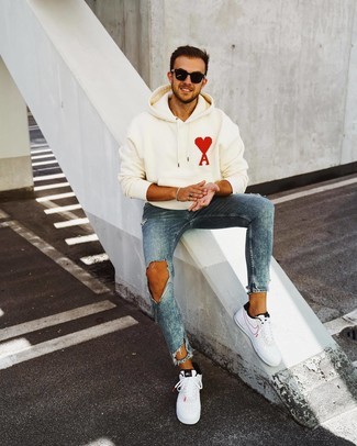 How to wear: white print hoodie, blue ripped skinny jeans, white and black leather low top sneakers, black sunglasses