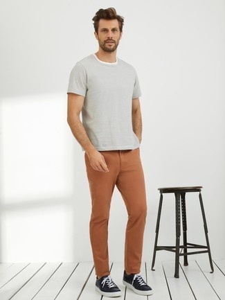 How to Wear Tobacco Chinos: A white horizontal striped crew-neck t-shirt and tobacco chinos are the kind of a fail-safe off-duty look that you need when you have zero time. Black leather low top sneakers make this look whole.