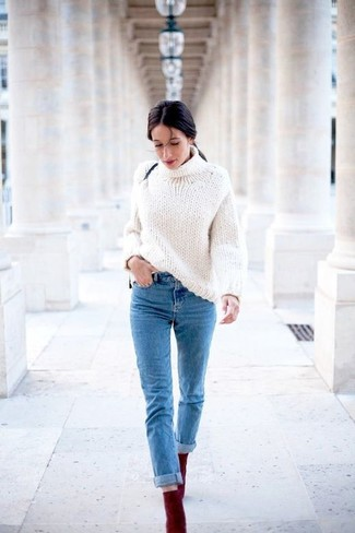 This combo of a white knit turtleneck and blue jeans will attract attention for all the right reasons. Complement this look with oxblood suede ankle boots.