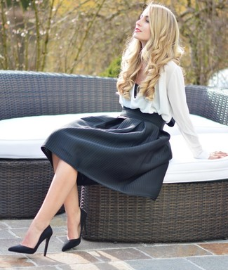 A nicely put together combination of a white long sleeve blouse and a black full skirt will set you apart effortlessly. Round off this look with black suede pumps.