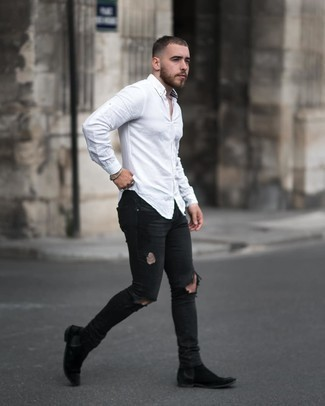 Black Ripped Skinny Jeans Outfits For Men: We're all looking for comfort when it comes to styling, and this contemporary combo of a white long sleeve shirt and black ripped skinny jeans is a great example of that. Black suede chelsea boots will immediately class up even your most comfortable clothes.