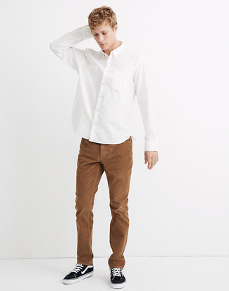 Brown Corduroy Chinos Warm Weather Outfits: Go for a straightforward yet cool and relaxed option by combining a white long sleeve shirt and brown corduroy chinos. To inject a more casual aesthetic into this look, add a pair of black and white canvas low top sneakers to the mix.