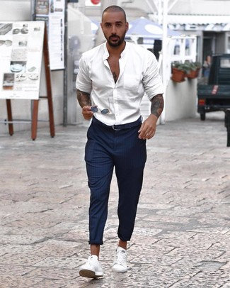 How to wear: white long sleeve shirt, navy vertical striped chinos, white low top sneakers, navy leather belt