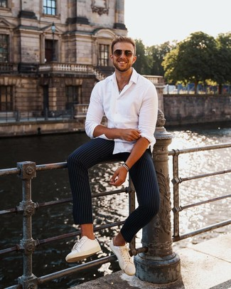 How to wear: white long sleeve shirt, navy vertical striped chinos, white leather low top sneakers, brown sunglasses