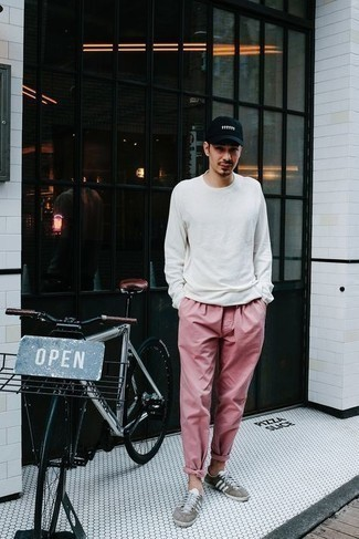 T-shirt Outfits For Men: Such must-haves as a t-shirt and pink chinos are an easy way to infuse effortless cool into your casual arsenal. Ramp up this look by rounding off with grey canvas low top sneakers.