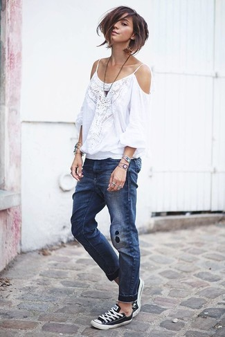 Go for a white lace off shoulder dress and navy ripped boyfriend jeans if you're after an outfit idea for when you want to look casually cool. Dress up your getup with monochrome canvas low top sneakers. This ensemble is a goofproof option if you're on the hunt for a great, summer-ready combo.