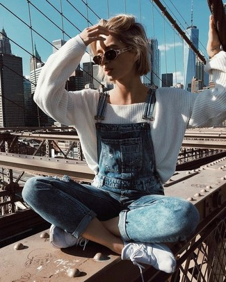 How to wear: white oversized sweater, blue denim overalls, white athletic shoes, dark brown sunglasses