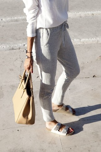 Pair a peasant blouse with grey sweatpants for a casual get-up. Finish off your look with white leather flat sandals.