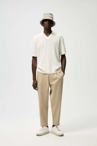 White and Black T-shirt with Polo Outfits For Men: A white and black t-shirt and khaki chinos matched together are a perfect match. White leather low top sneakers will inject a touch of elegance into an otherwise mostly dressed-down look.