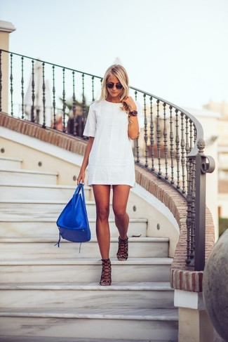 Reach for a white shift dress to achieve a neat and proper look. For shoes, go for a pair of black suede heeled sandals. What better idea for a warm day?