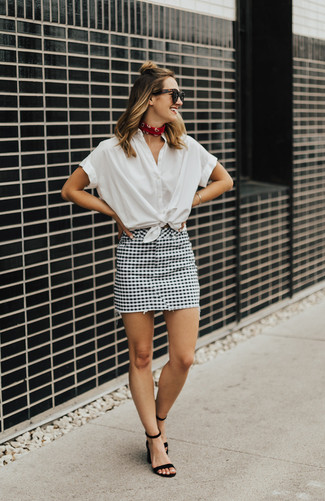 Dress in a white short sleeve button down shirt and a monochrome check mini skirt for a Sunday lunch with friends. Elevate this ensemble with black suede heeled sandals.