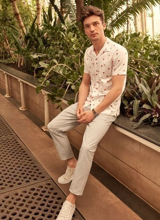 How to Wear White Low Top Sneakers For Men: A white print short sleeve shirt and grey chinos are a cool go-to outfit to keep in your menswear collection. Our favorite of a great number of ways to complement this ensemble is a pair of white low top sneakers.