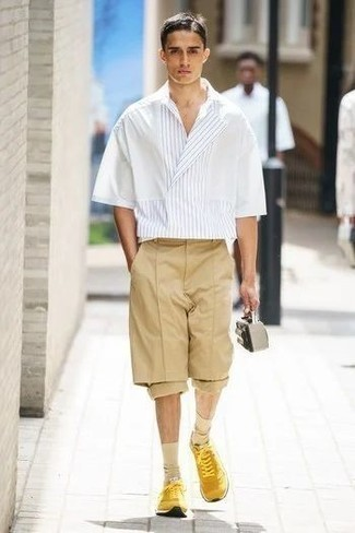 Shorts Outfits For Men: A white vertical striped short sleeve shirt and shorts? This is an easy-to-achieve outfit that any man could rock on a daily basis. Mustard athletic shoes are the simplest way to infuse a sense of stylish effortlessness into your ensemble.