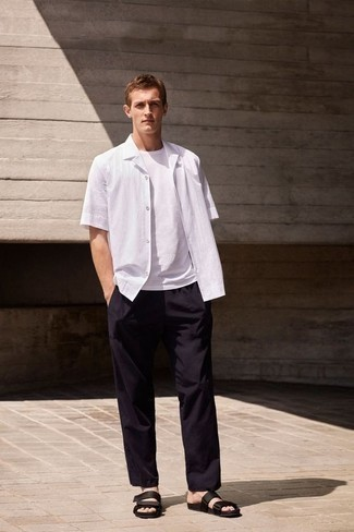 How to Wear a White Short Sleeve Shirt For Men: This combination of a white short sleeve shirt and black chinos combines comfort and practicality and helps you keep it low-key yet current. If you want to effortlessly play down your look with one single item, why not go for a pair of black canvas sandals?