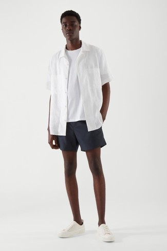 Navy Shorts Outfits For Men: This combo of a white short sleeve shirt and navy shorts is hard proof that a safe casual ensemble can still be really interesting. Complete your getup with white canvas low top sneakers to pull the whole thing together.