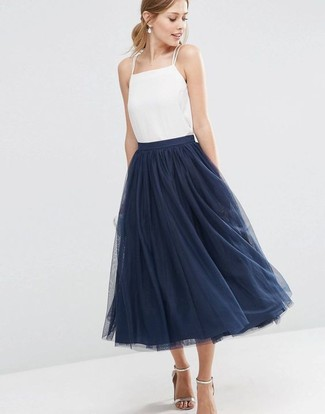 How to Wear a Navy Full Skirt: Combining a white silk tank with a navy full skirt is a wonderful choice for a casual outfit. Ramp up the appeal of your getup by wearing a pair of silver leather heeled sandals.