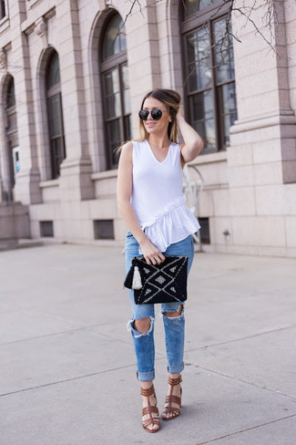 How to wear: white ruffle sleeveless top, blue ripped skinny jeans, brown leather heeled sandals, black knit clutch