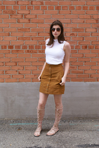 This combination of a white sleeveless turtleneck and a button skirt is clean, chic and oh-so-easy to copy! Beige leather knee high gladiator sandals will give your look an on-trend feel. This here is proof that it is indeed possible survive the unbearable heat, all while looking fresh and clean.