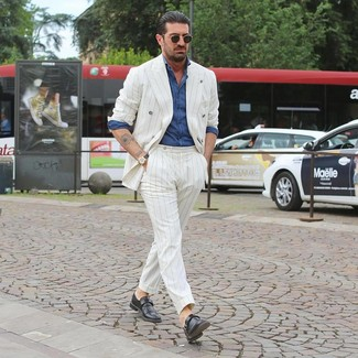 How to Wear a White Vertical Striped Suit: You'll be surprised at how easy it is for any gentleman to get dressed this way. Just a white vertical striped suit and a blue chambray long sleeve shirt. A pair of black leather monks effortlesslly ups the classy factor of your look.