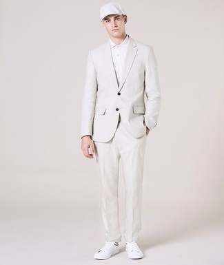 How to Wear a Flat Cap For Men: Rock a white suit with a flat cap for a laid-back kind of polish. A pair of white leather low top sneakers is the glue that ties your getup together.