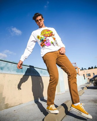 How to wear: white print sweatshirt, tobacco jeans, mustard canvas low top sneakers, white socks