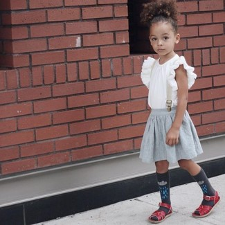 How to Wear a Grey Skirt For Girls: A white ruffle tank top and a grey skirt are a great outfit for your kid to go out exploring. As far as footwear is concerned, let your little girl opt for a pair of red sandals.