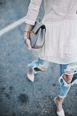 Opt for a Topshop Lace Up Choker Boyfriend Tunic Top and light blue ripped boyfriend jeans for a casual-cool vibe. To add oomph to your outfit, complete with beige leather pumps. You can bet this combo is great when warmer days are here.