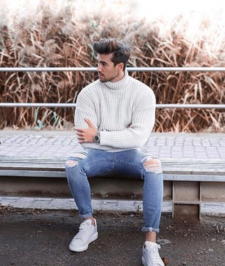 How to Wear Blue Ripped Skinny Jeans For Men: If you enjoy the comfort look, choose a white knit turtleneck and blue ripped skinny jeans. To bring a bit of classiness to this ensemble, introduce a pair of white leather low top sneakers to the equation.