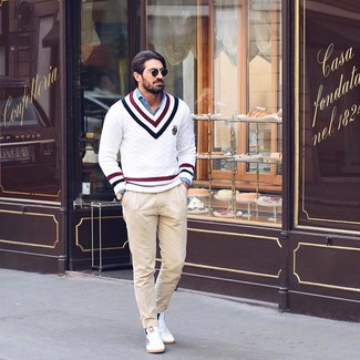 How to wear: white chevron v-neck sweater, blue chambray long sleeve shirt, beige chinos, white low top sneakers