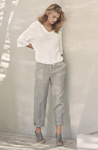 How to Wear a White and Blue V-neck Sweater For Women: Go for a pared down yet casually stylish choice pairing a white and blue v-neck sweater and grey linen wide leg pants. Add a pair of grey leather wedge sandals to the equation et voila, your getup is complete.