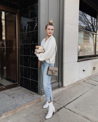 White Leather Ankle Boots Outfits: A white v-neck sweater and light blue jeans are the perfect foundation for a totaly stylish ensemble. Take an otherwise everyday look down a classier path by sporting white leather ankle boots.