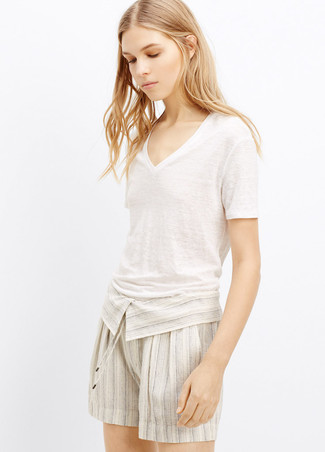 Consider pairing a v-neck t-shirt with beige linen shorts to create a chic, glamorous look. We're loving how great this outfit is come summertime.